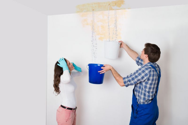 young woman standing with worker collecting water in bucket from ceiling in house